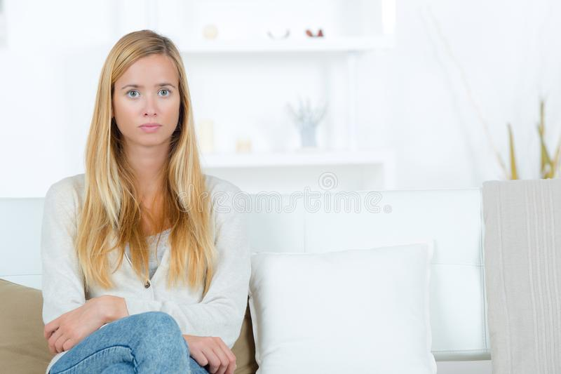 Όμορφη νέα ξανθή συνεδρίαση γυναικών πορτρέτου στον καναπέ στοκ εικόνες