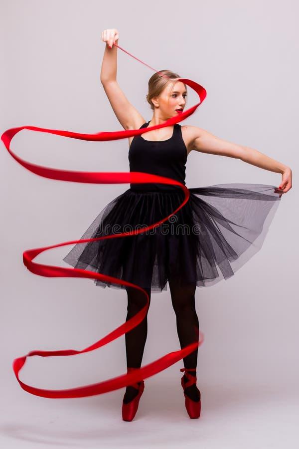 Όμορφη νέα ξανθή gymnast μπαλέτου γυναικών άσκηση calilisthenics κατάρτισης με την κόκκινη κορδέλλα με τα κόκκινα παπούτσια στοκ εικόνα