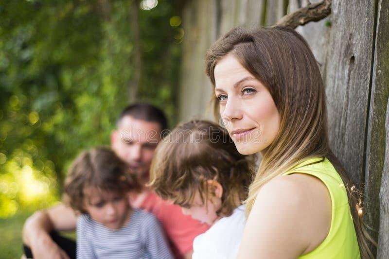Όμορφη νέα οικογένεια ενάντια στον παλαιό ξύλινο φράκτη χρωματισμένο καλοκαίρι φύσης χεριών γίνοντα απεικόνιση στοκ εικόνες με δικαίωμα ελεύθερης χρήσης