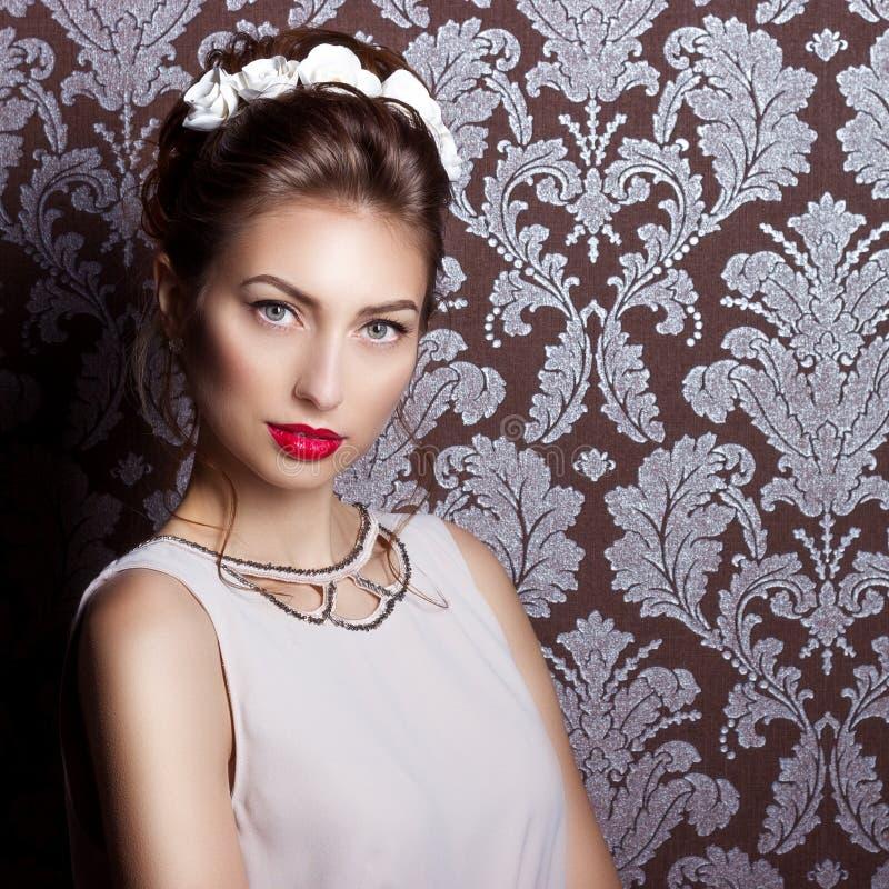 Όμορφη νέα προκλητική κομψή γυναίκα με τα κόκκινα χείλια, όμορφο μοντέρνο hairstyle με τα άσπρα λουλούδια στην τρίχα της, ο τρόπο στοκ εικόνες