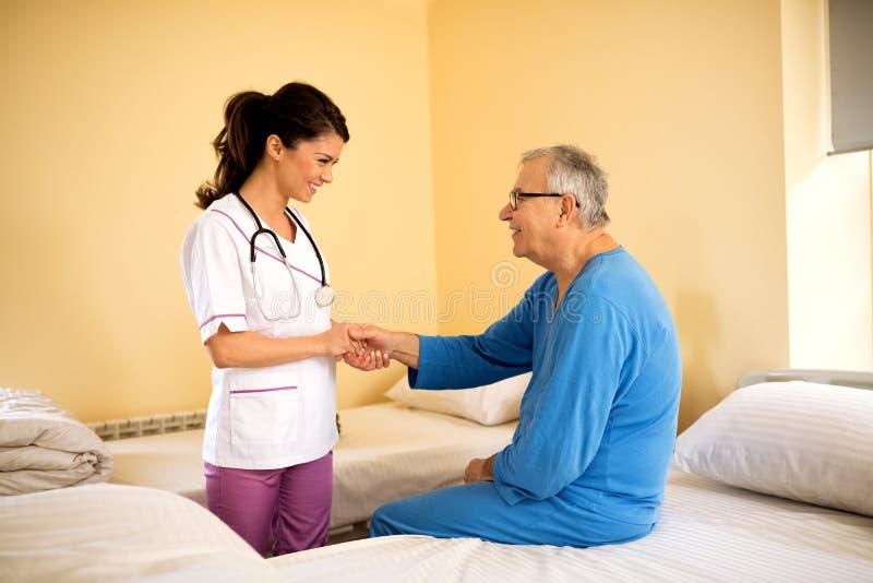 Όμορφη νέα προσεκτική ομιλία νοσοκόμων και ασθενής κονσολών στο nur στοκ εικόνα