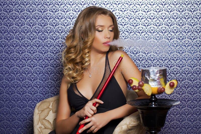 Όμορφη νέα σγουρή ξανθή γυναίκα που στηρίζεται στο δωμάτιο hookah στοκ φωτογραφία με δικαίωμα ελεύθερης χρήσης
