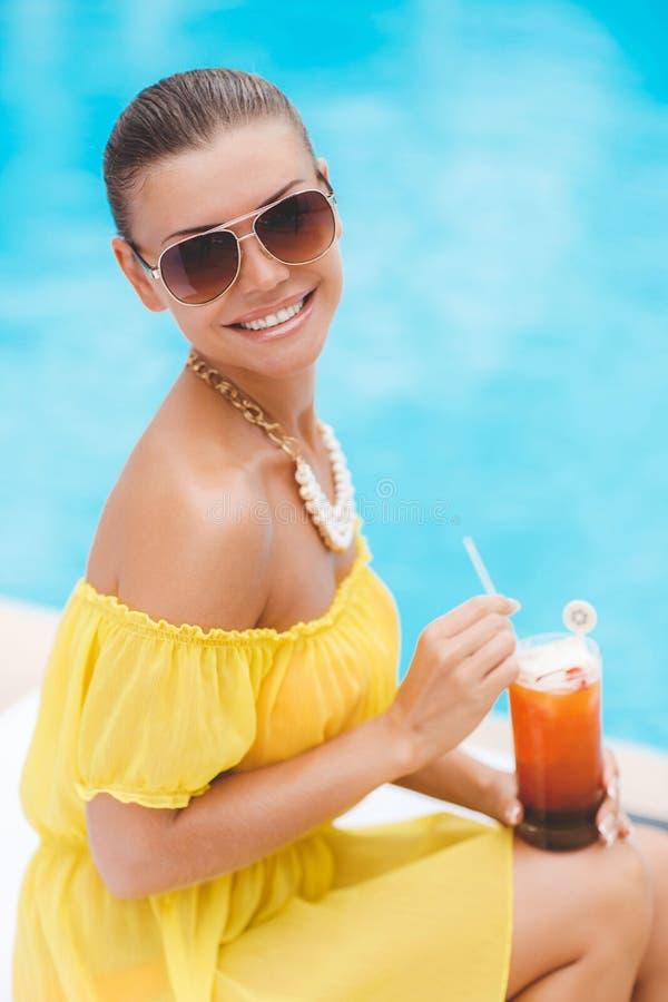Όμορφη νέα στηργμένος συνεδρίαση γυναικών με ένα ποτήρι του πορτοκαλιού κοκτέιλ από την πισίνα με το μπλε νερό στο τροπικό θέρετρ στοκ φωτογραφίες