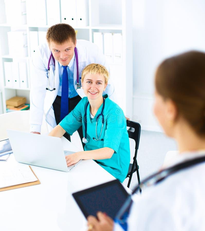 Όμορφη νέα συνεδρίαση γιατρών χαμόγελου θηλυκή στο γραφείο στοκ φωτογραφίες