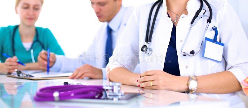 Όμορφη νέα συνεδρίαση γιατρών χαμόγελου θηλυκή στο γραφείο στοκ εικόνες