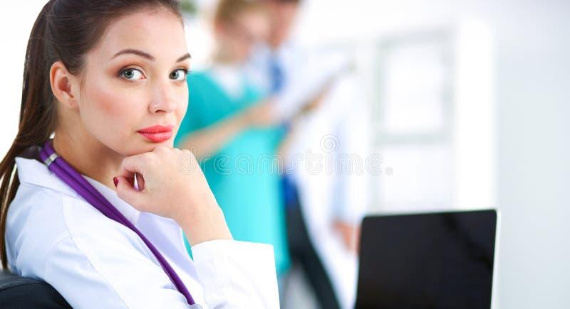 Όμορφη νέα συνεδρίαση γιατρών χαμόγελου θηλυκή στο γραφείο στοκ φωτογραφία με δικαίωμα ελεύθερης χρήσης