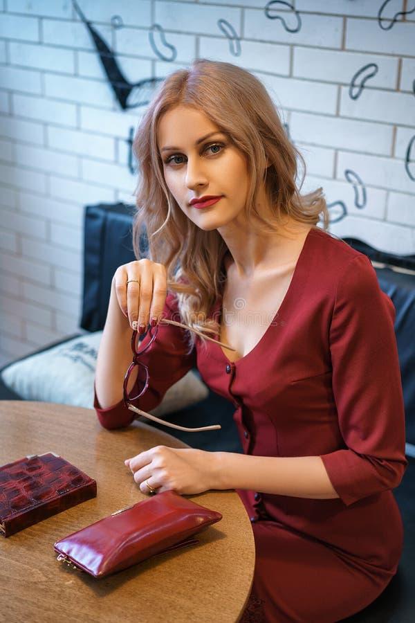Όμορφη νέα συνεδρίαση γυναικών σε έναν πίνακα με ένα σημειωματάριο και ένα τηλέφωνο στοκ εικόνες