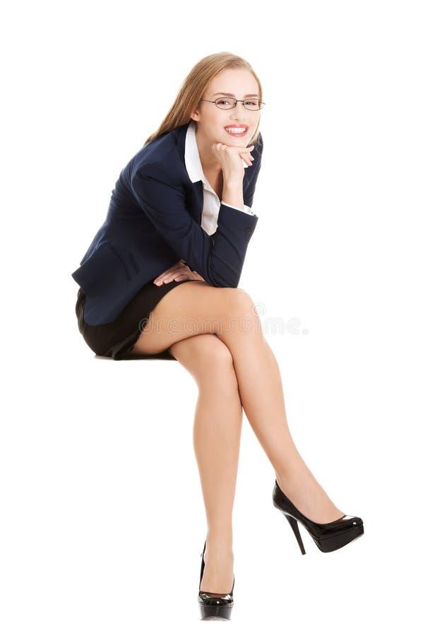 Όμορφη νέα συνεδρίαση επιχειρησιακών γυναικών σε μια καρέκλα στοκ φωτογραφία