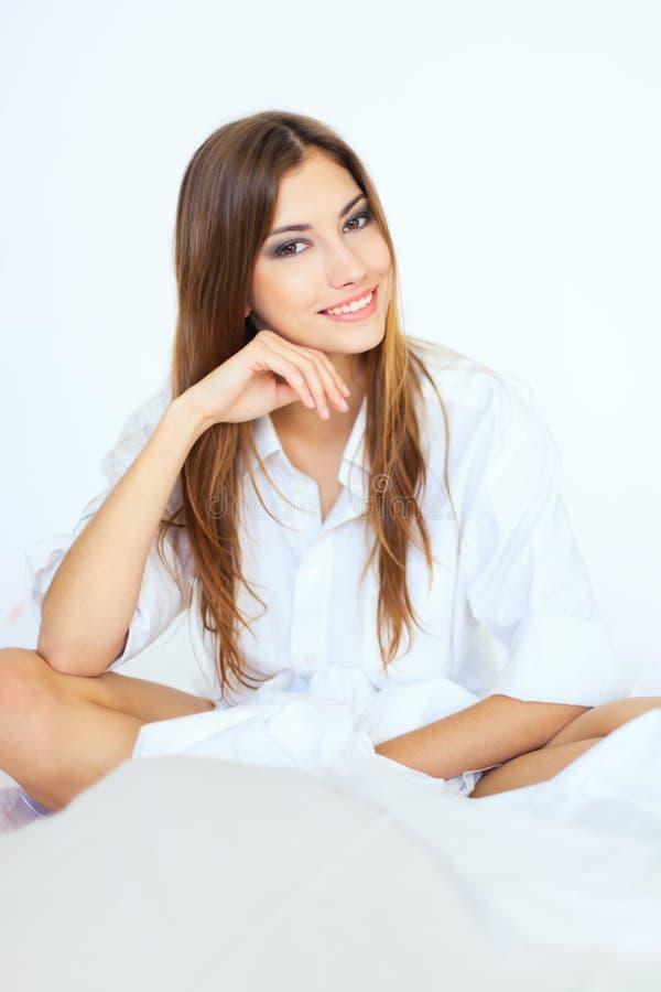 Όμορφη νέα συνεδρίαση γυναικών στο κρεβάτι στοκ φωτογραφίες με δικαίωμα ελεύθερης χρήσης
