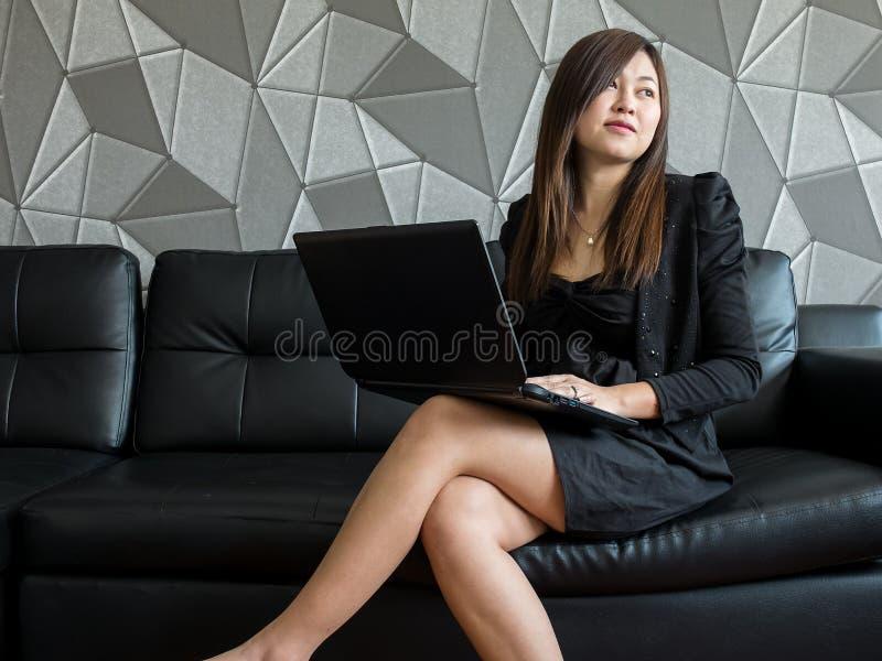 Όμορφη νέα συνεδρίαση επιχειρησιακών γυναικών της Ασίας στον καναπέ, που λειτουργεί με το φορητό προσωπικό υπολογιστή και το μαύρ στοκ εικόνες