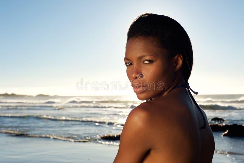 Όμορφη νέα τοποθέτηση μαύρων γυναικών στην παραλία στοκ εικόνα