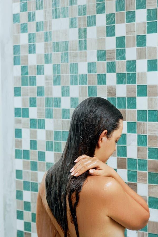Όμορφη νέα τρίχα πλύσης γυναικών με το shampo στο ντους r στοκ εικόνες με δικαίωμα ελεύθερης χρήσης