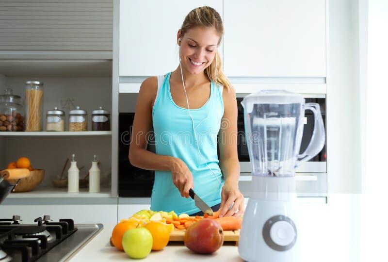 Όμορφη νέα φίλαθλη γυναίκα που κόβει μερικά λαχανικά και φρούτα ακούοντας τη μουσική στην κουζίνα στοκ εικόνα