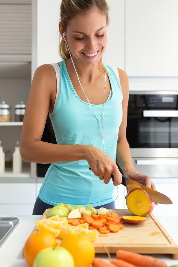 Όμορφη νέα φίλαθλη γυναίκα που κόβει μερικά λαχανικά και φρούτα ακούοντας τη μουσική στην κουζίνα στοκ εικόνα με δικαίωμα ελεύθερης χρήσης