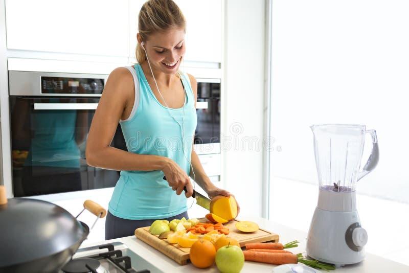 Όμορφη νέα φίλαθλη γυναίκα που κόβει μερικά λαχανικά και φρούτα ακούοντας τη μουσική στην κουζίνα στοκ φωτογραφία με δικαίωμα ελεύθερης χρήσης