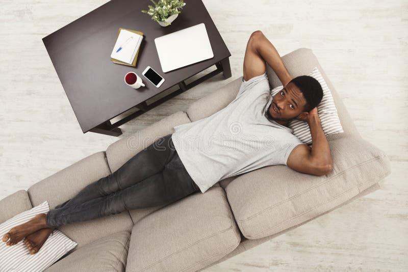 Όμορφη νέα χαλάρωση ατόμων αφροαμερικάνων στον καναπέ στο σπίτι στοκ φωτογραφία με δικαίωμα ελεύθερης χρήσης