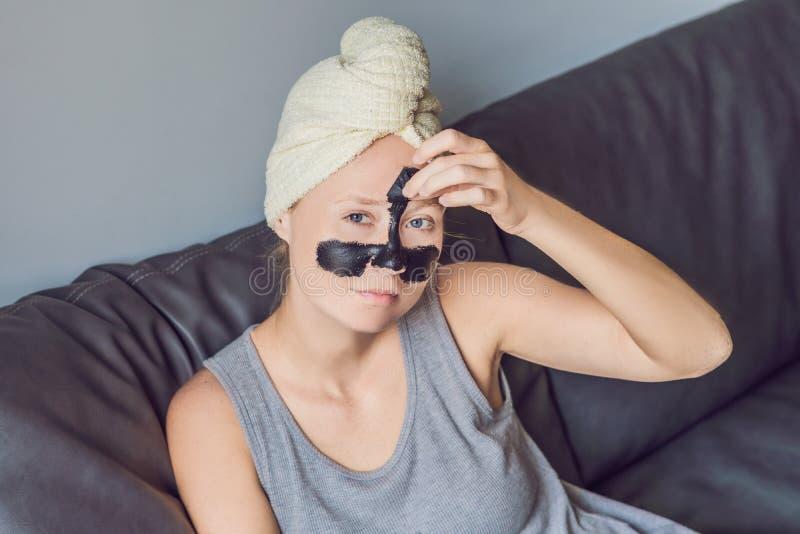 Όμορφη νέα χαλάρωση γυναικών με τη μάσκα προσώπου στο σπίτι ευτυχής χαρά στοκ εικόνα με δικαίωμα ελεύθερης χρήσης