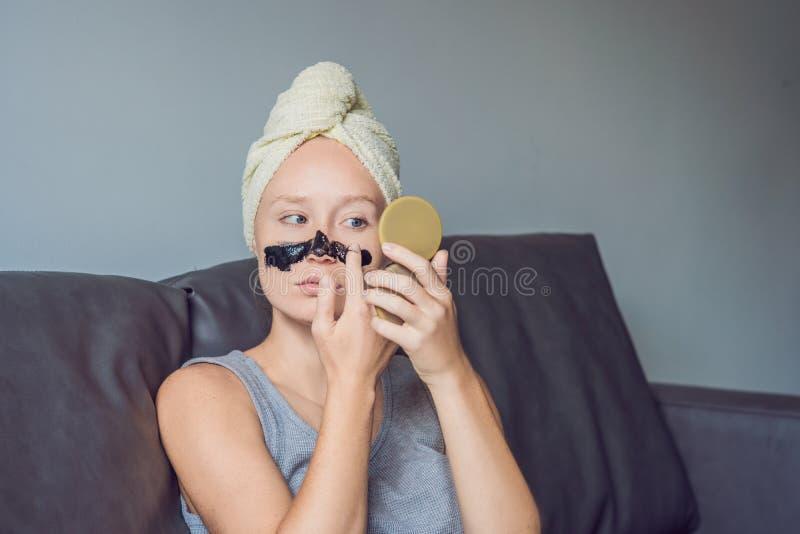Όμορφη νέα χαλάρωση γυναικών με τη μάσκα προσώπου στο σπίτι Ευτυχής χαρούμενη γυναίκα που εφαρμόζει τη μαύρη μάσκα στο πρόσωπο στοκ φωτογραφία