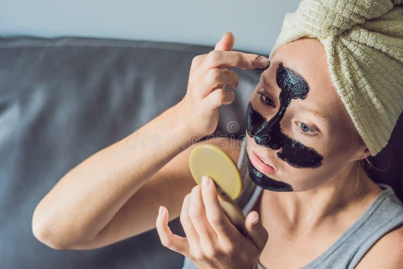 Όμορφη νέα χαλάρωση γυναικών με τη μάσκα προσώπου στο σπίτι Ευτυχής χαρούμενη γυναίκα που εφαρμόζει τη μαύρη μάσκα στο πρόσωπο στοκ εικόνα με δικαίωμα ελεύθερης χρήσης
