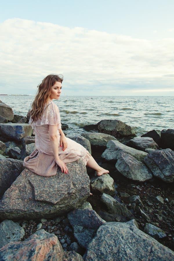 Όμορφη νέα χαλάρωση γυναικών στην ωκεάνια ακτή, ρομαντικό πορτρέτο ομορφιάς Όμορφη συνεδρίαση κοριτσιών στους βράχους και να ονει στοκ φωτογραφία
