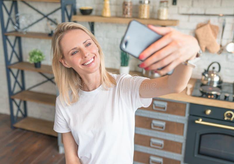 Όμορφη νέα χαμογελώντας γυναίκα που κάνει selfie με το τηλέφωνο στην κουζίνα r να μαγειρεψει στο σπίτι Φθορά του άσπρου πουκάμισο στοκ εικόνες