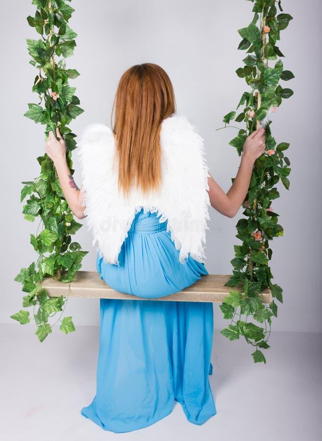 Όμορφη νέα leggy κοκκινομάλλης γυναίκα σε ένα μακρύ μπλε φόρεμα σε μια ταλάντευση, ξύλινη ταλάντευση που αναστέλλεται από μια κάν στοκ εικόνα με δικαίωμα ελεύθερης χρήσης