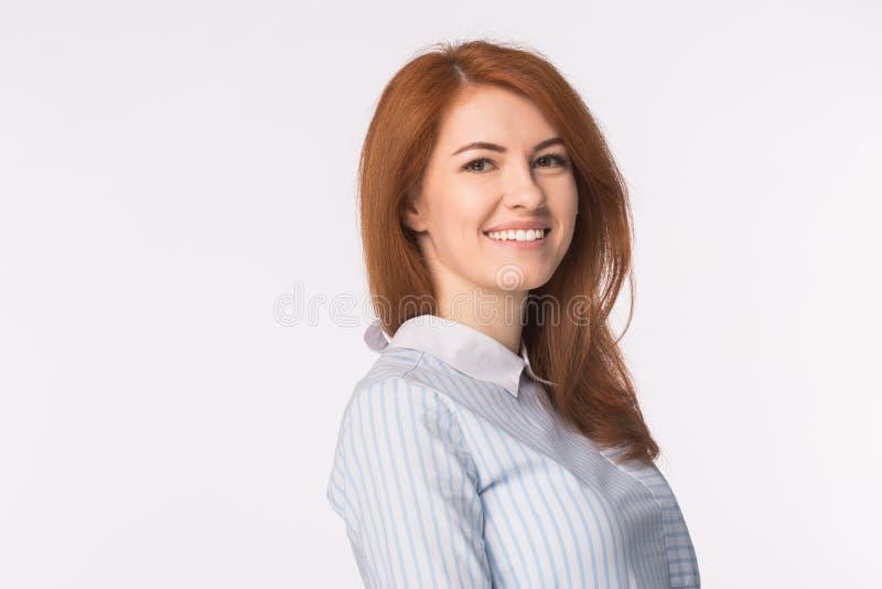 Όμορφη νέα redhead χαμογελώντας γυναίκα που απομονώνεται στο λευκό στοκ φωτογραφίες