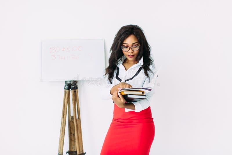 Όμορφη νεαρή Αφρικανή χαμογελαστή δασκάλα που κρατά έγγραφα, βιβλία, ÏƒÏ στοκ εικόνες