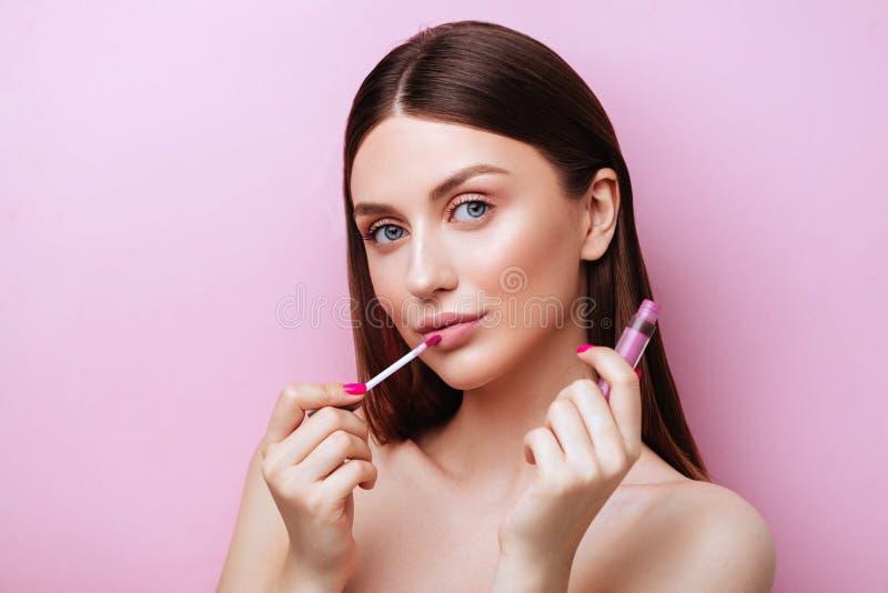 Όμορφη νεαρή γυναίκα με κραγιόν στο ροζ φόντο στοκ εικόνες