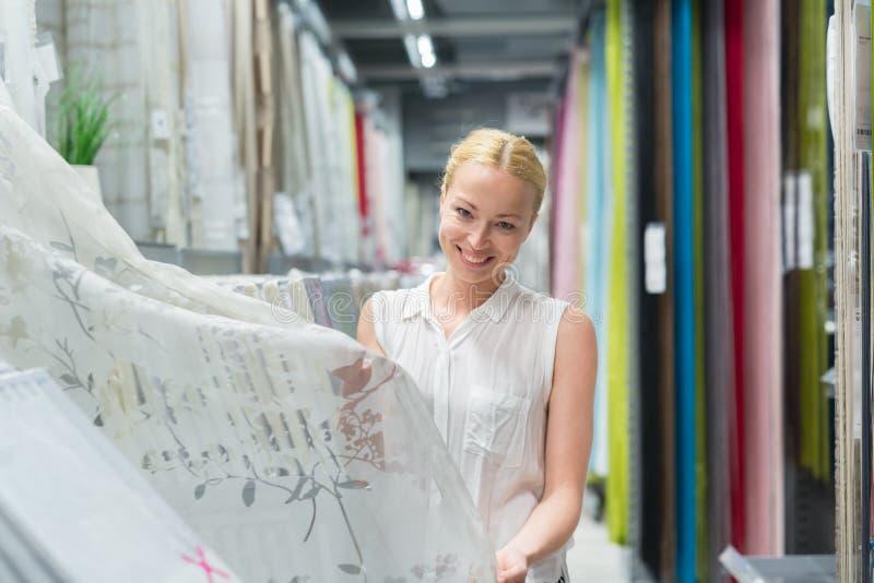 Όμορφη νοικοκυρά που αγοράζει τις άσπρες κουρτίνες στο κατάστημα επιπλώσεων εγχώριων ντεκόρ στοκ εικόνες
