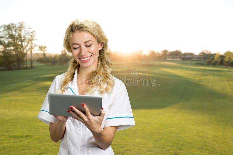 Όμορφη νοσοκόμα με την ταμπλέτα PC υπαίθρια στοκ εικόνες