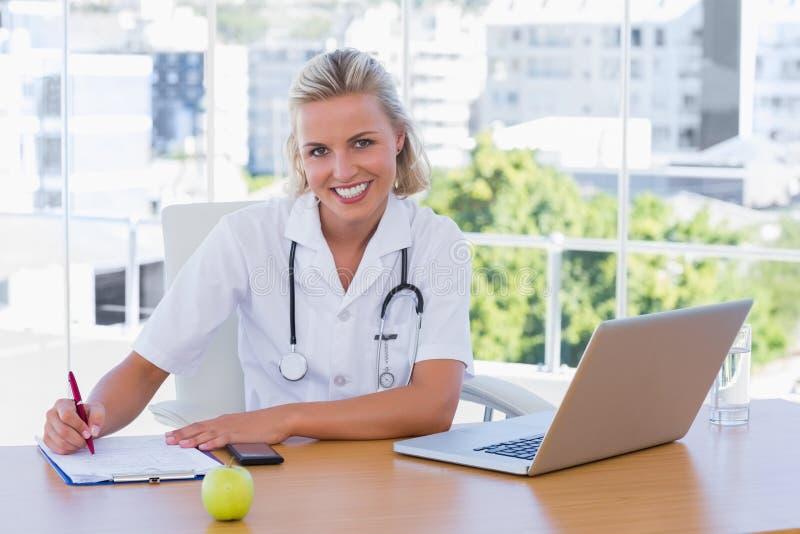 Όμορφη νοσοκόμα που γράφει σε ένα σημειωματάριο στο γραφείο της στοκ φωτογραφία με δικαίωμα ελεύθερης χρήσης
