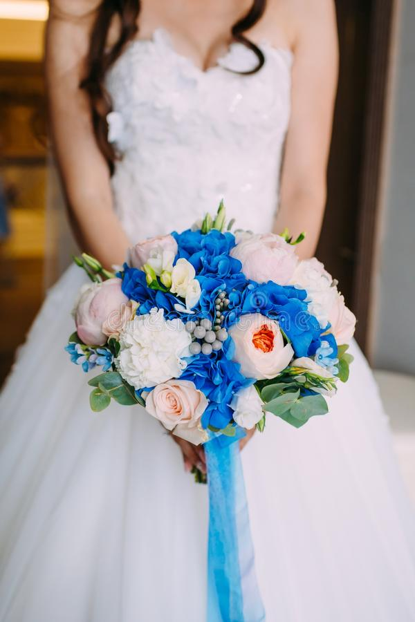 Όμορφη νυφική ανθοδέσμη με τα κρεμώδη τριαντάφυλλα και peonies και τα μπλε hydrangeas Γαμήλιο πρωί Κινηματογράφηση σε πρώτο πλάνο στοκ εικόνες