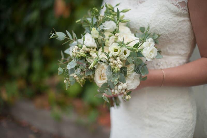 Όμορφη νυφική σύγχρονη ανθοδέσμη στα χέρια της νύφης στοκ εικόνα