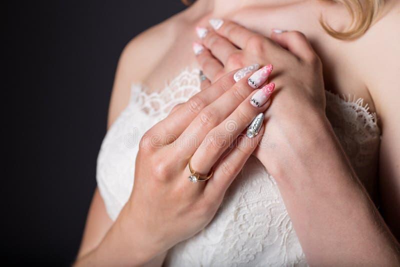 Όμορφη νύφη κοριτσιών χεριών στο άσπρο γαμήλιο φόρεμα με τα ακρυλικά καρφιά και το λεπτό σχέδιο και rhinestones στοκ εικόνα με δικαίωμα ελεύθερης χρήσης