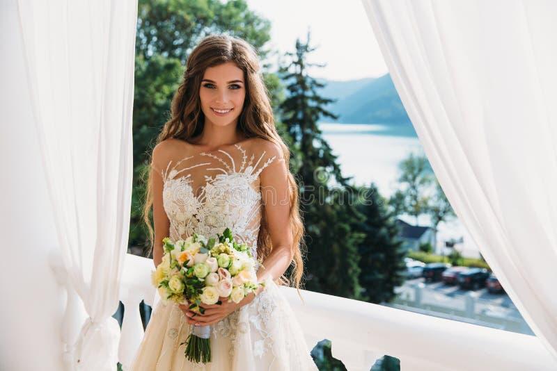 Όμορφη νύφη με την όμορφη ανθοδέσμη των λουλουδιών στα χέρια Ελκυστική νέα γυναίκα στο άσπρο φόρεμα με τη γαμήλια σύνθεση επάνω στοκ φωτογραφία με δικαίωμα ελεύθερης χρήσης