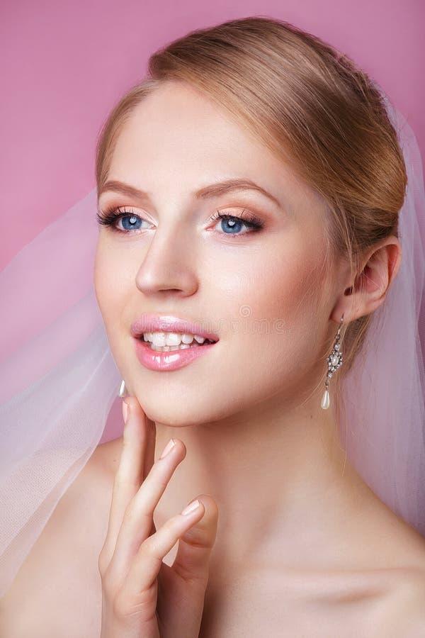 Όμορφη νύφη με το γάμο μόδας hairstyle - στο ρόδινο υπόβαθρο Πορτρέτο κινηματογραφήσεων σε πρώτο πλάνο της νέας πανέμορφης νύφης  στοκ φωτογραφία με δικαίωμα ελεύθερης χρήσης