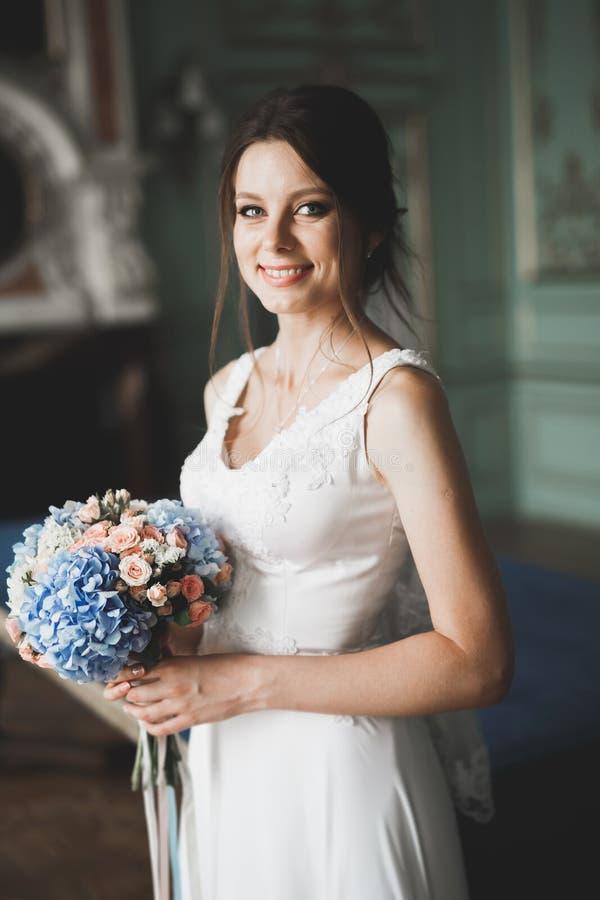 Όμορφη νύφη πολυτέλειας στο κομψό άσπρο φόρεμα στοκ εικόνες