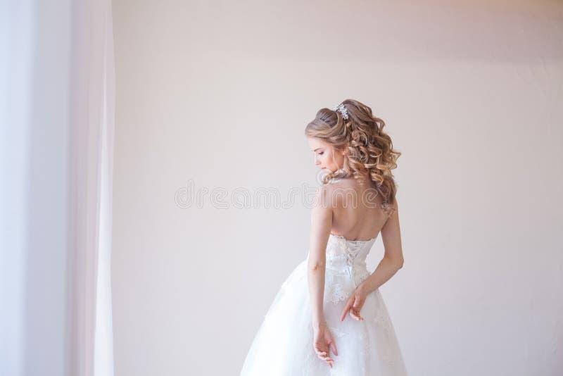 Όμορφη νύφη που θέτει το γάμο hairstyle και το φόρεμα στοκ φωτογραφίες