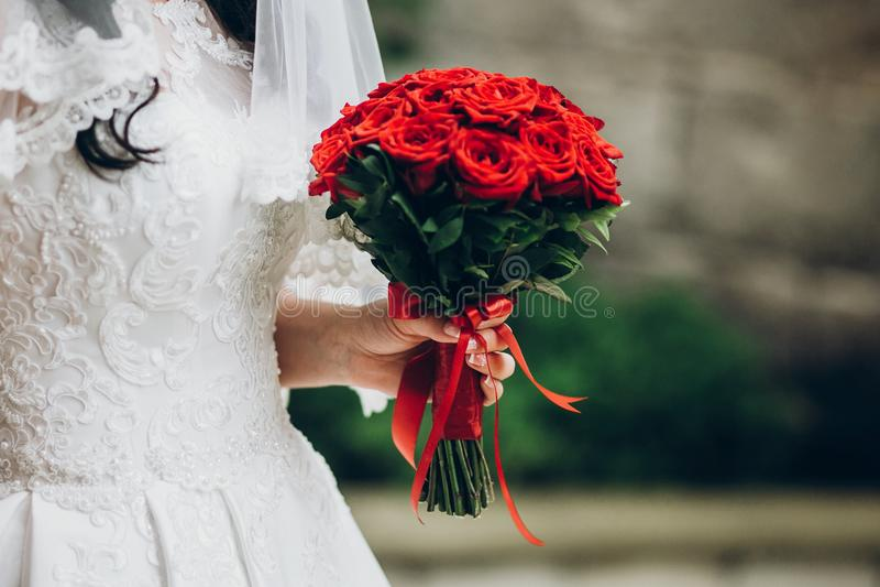 Όμορφη νύφη που κρατά τη μοντέρνη ανθοδέσμη το πρωί κόκκινος αυξήθηκε στοκ φωτογραφία