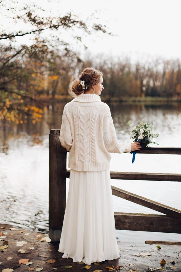Όμορφη νύφη που στέκεται μόνο στο αχλάδι ποταμών στο φόρεμα και το πουλόβερ στοκ εικόνες