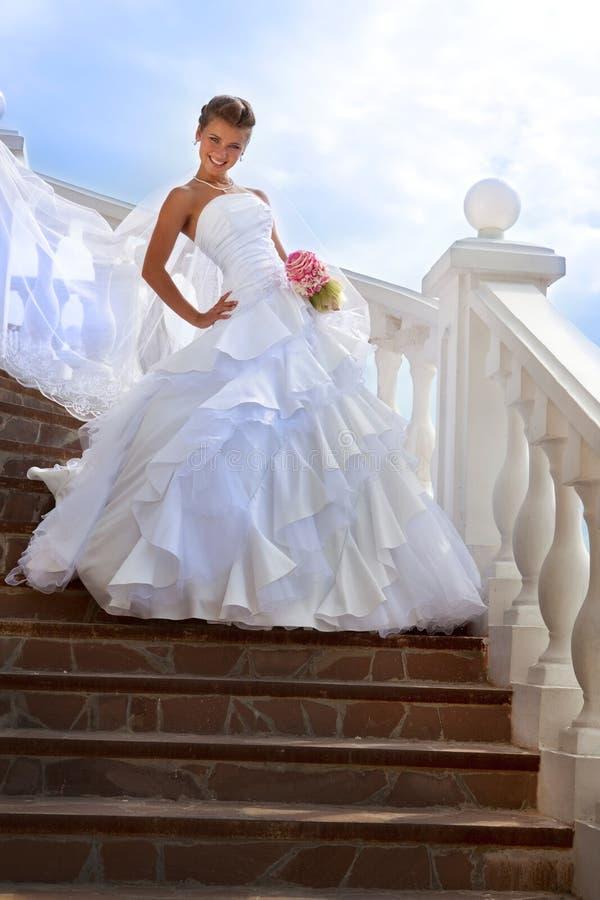 Όμορφη νύφη που στέκεται στα σκαλοπάτια στην ηλιόλουστη ημέρα στοκ εικόνα