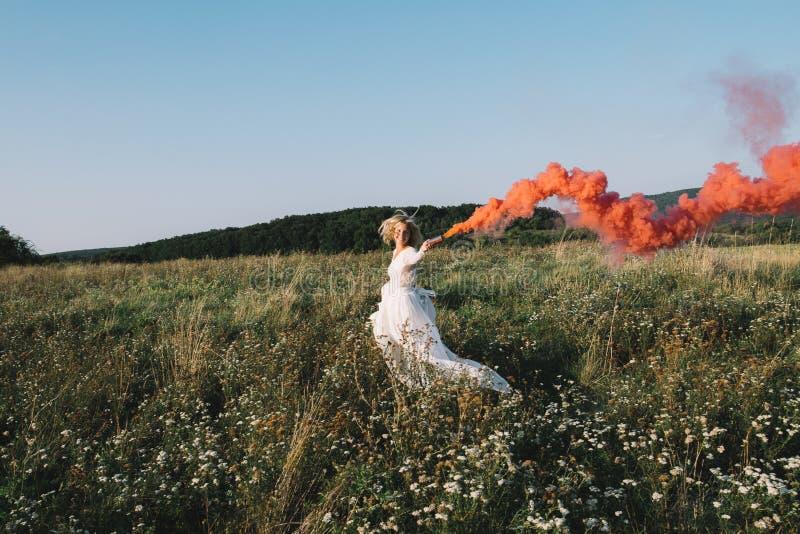 Όμορφη νύφη που τρέχει υπαίθρια με τον κόκκινο καπνό στοκ εικόνες με δικαίωμα ελεύθερης χρήσης