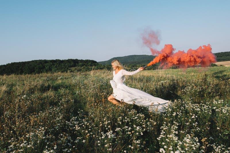 Όμορφη νύφη που τρέχει υπαίθρια με τον κόκκινο καπνό στοκ εικόνες