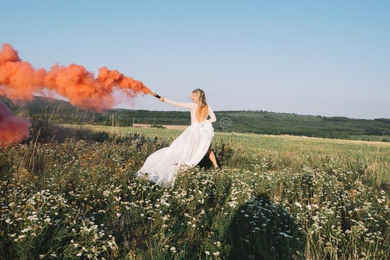 Όμορφη νύφη που τρέχει υπαίθρια με τον κόκκινο καπνό στοκ φωτογραφία με δικαίωμα ελεύθερης χρήσης