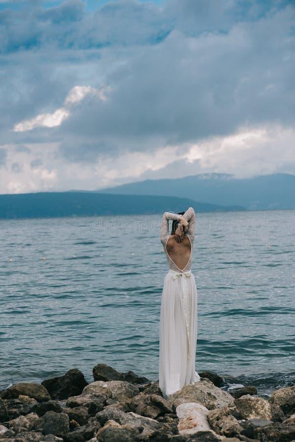 Όμορφη νύφη που υπερασπίζεται τη θάλασσα στοκ φωτογραφία