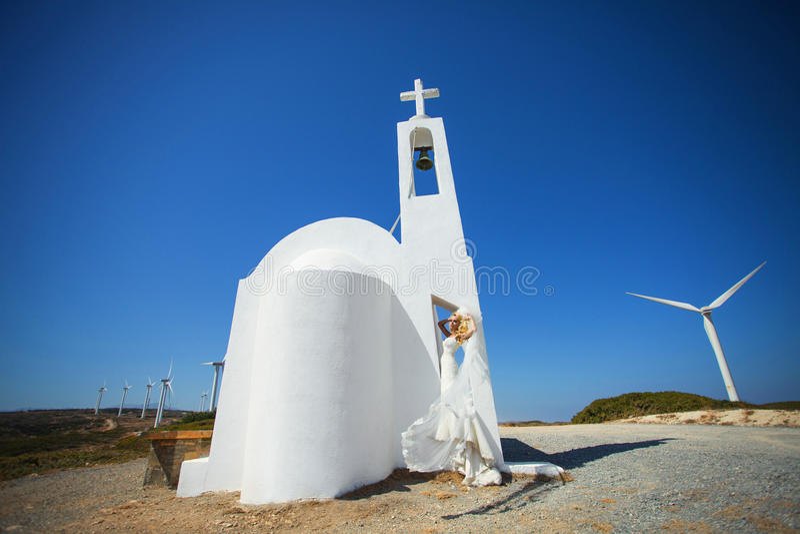 Όμορφη νύφη σε ένα γαμήλιο φόρεμα στην Ελλάδα με ένα μακρύ πέπλο στοκ φωτογραφίες