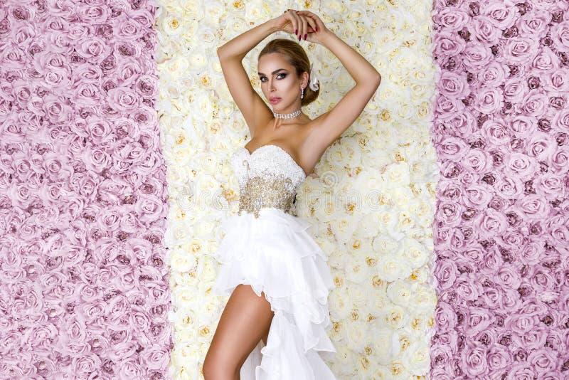 Όμορφη νύφη σε ένα ζαλίζοντας γαμήλιο φόρεμα με τη δαντέλλα Νέα γυναίκα ομορφιάς σε ένα υπόβαθρο των τριαντάφυλλων - εικόνα στοκ εικόνα