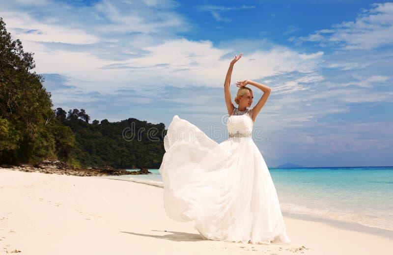 Όμορφη νύφη στην κομψή τοποθέτηση γαμήλιων φορεμάτων στην παραλία στην Ταϊλάνδη στοκ φωτογραφία