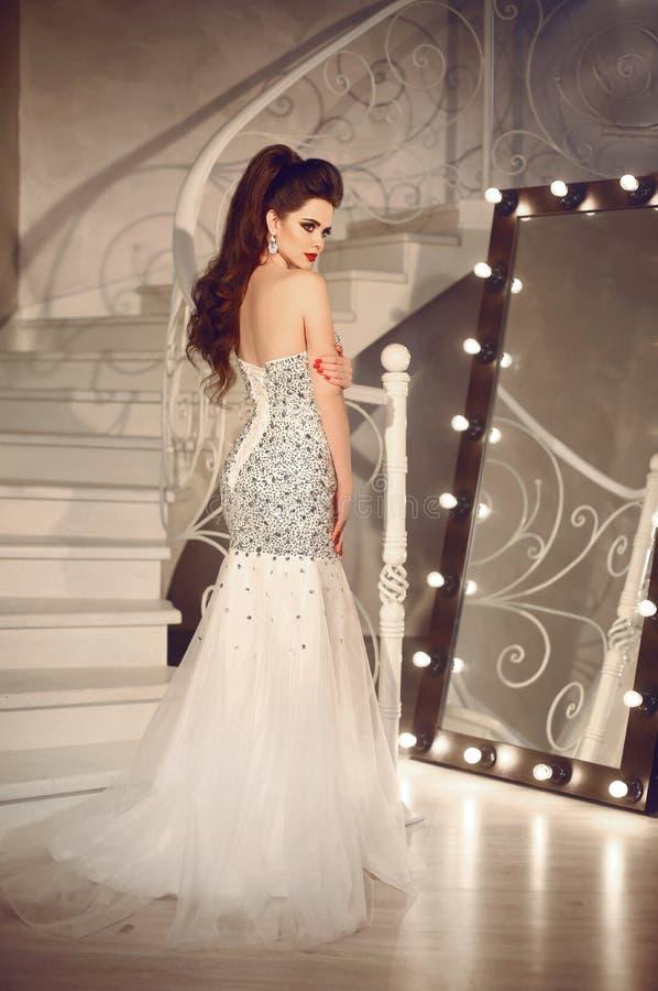 Όμορφη νύφη στην τοποθέτηση γαμήλιων φορεμάτων από τη σκάλα στο luxuriou στοκ φωτογραφίες